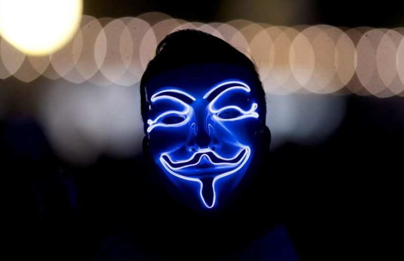 Face in the dark wearing the anonymous Guy Fawkes mask, with blue lights illuminating features.