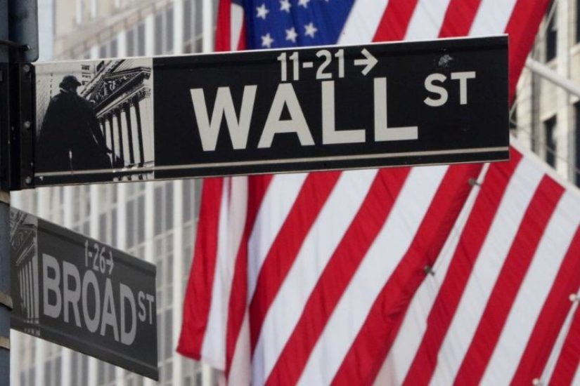 Wall Street road sign in front of american flag hanging off building flag pole