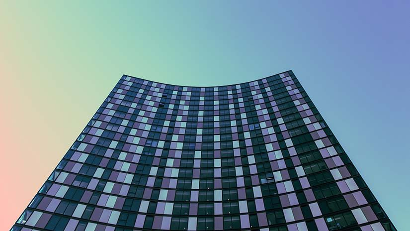 A down-up view of a tall curved glass building with a blue background