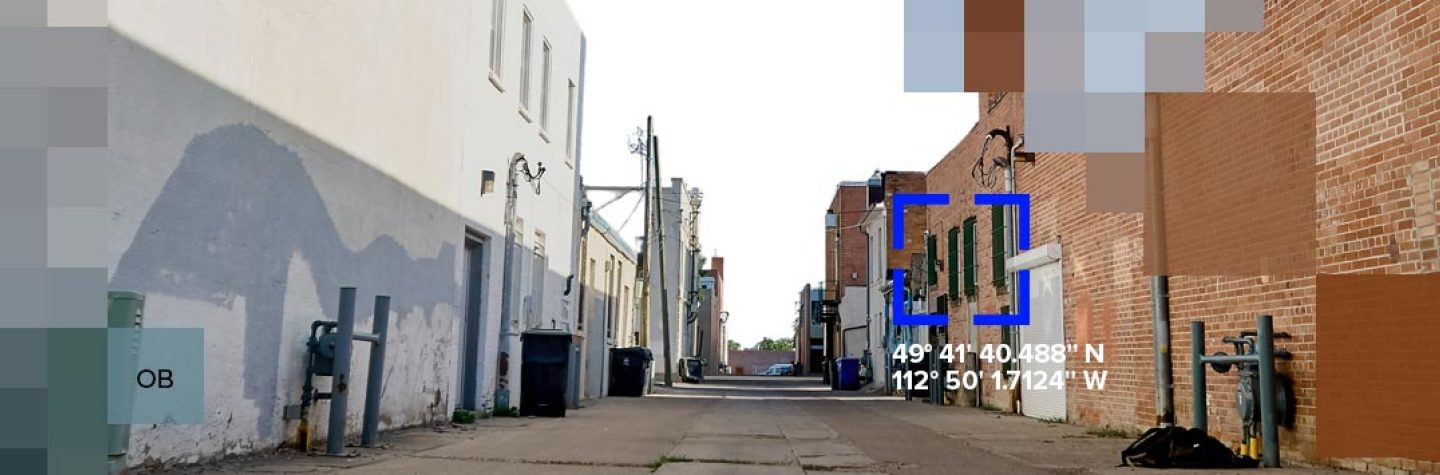 A backstreet between buildings with pixlated graphics
