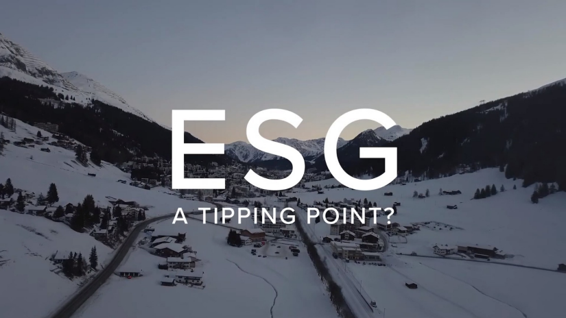 "Town in the middle of a snow covered mountain valley at dawn, with white text: ""ESG: A tipping point"""