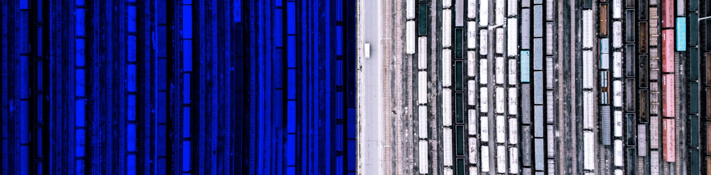 aerial view over train tracks with hundreds of industrial train cars.  Blue overlay over left half of the image.
