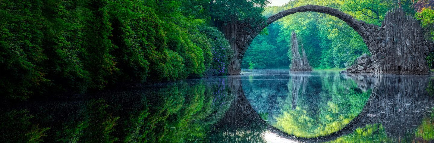 Arch bridge reflected over a calm river with green foliage surrounding