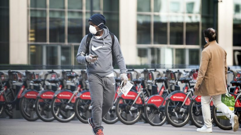 A man with a facemask on walks with bicycles lined up behind him