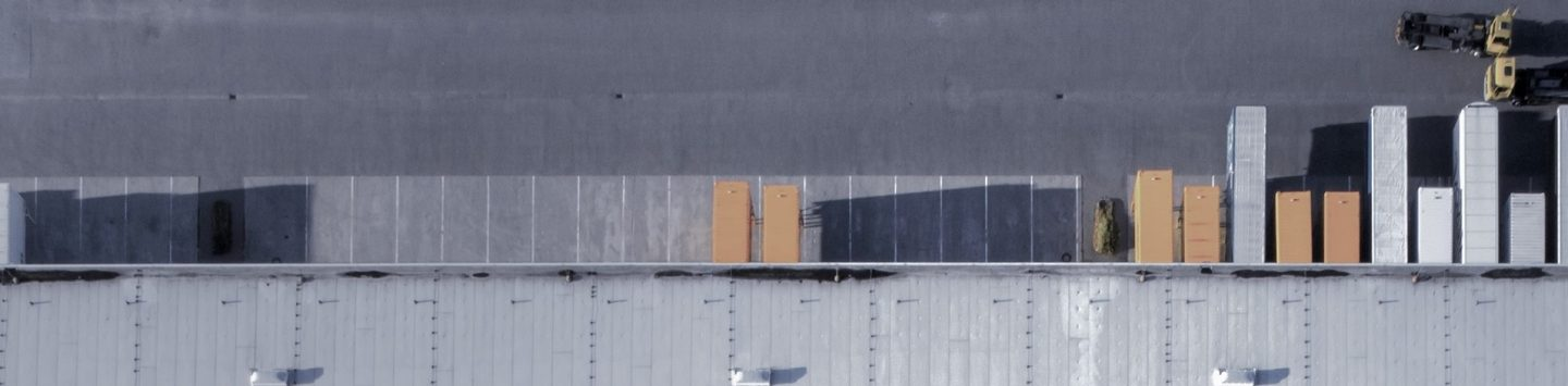 Arial shot of building parking lot with lorry containers parked at loading bays