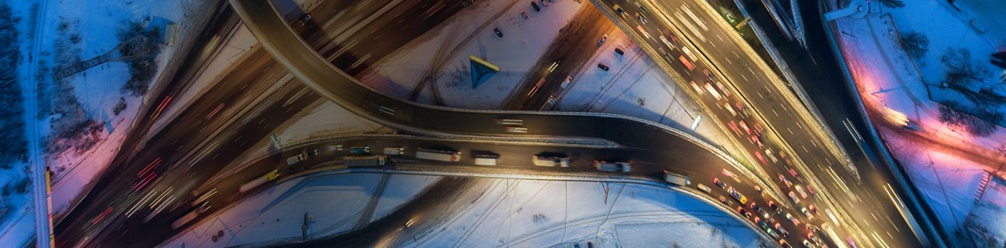 Aerial view of road in the modern city at night in winter. Top view of traffic in highway junction with illumination. Elevated road and interchange overpass. Busy intersection. Expressway and motorway