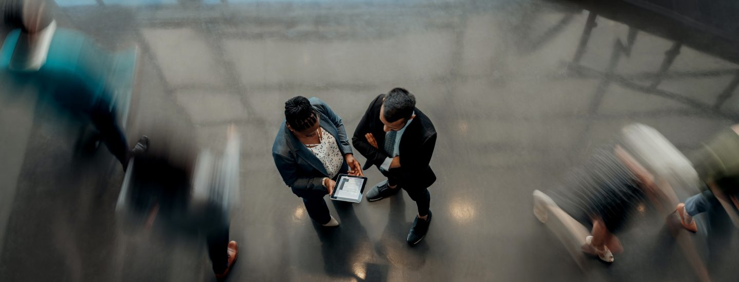 Woman and man in office environment looking at tablet, with people walking around them blurred.