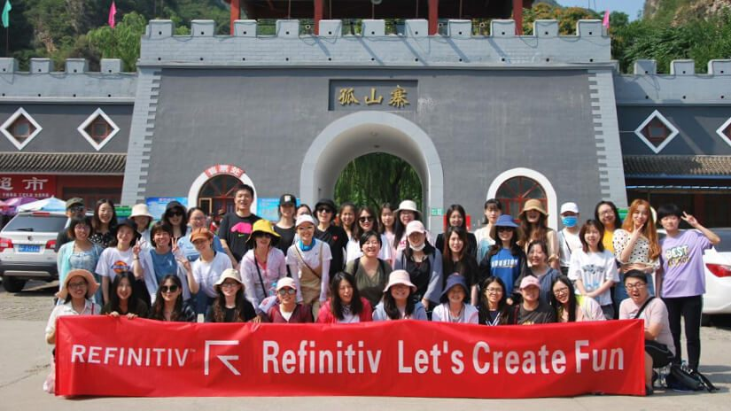 A group of people pose in front of a castle gatehouse. They are holding a long banner which reads Refinitiv lets create fun