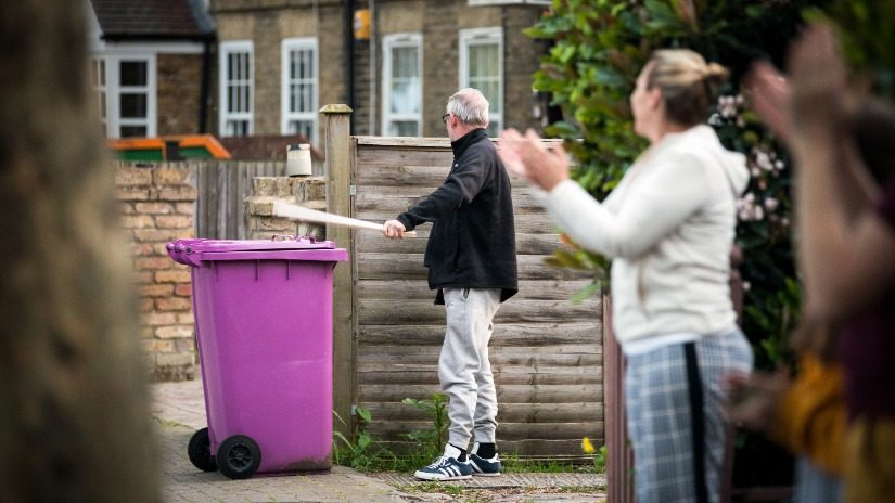 Woman claps whilst man bangs on bin lid with sticks.