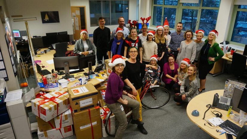 A group of people gathered in an office setting wearing Christmas headgear.