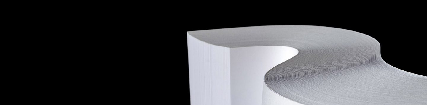 Studio photo of multiple sheets of rolled A4 paper stack (S-shaped ream) on black background.