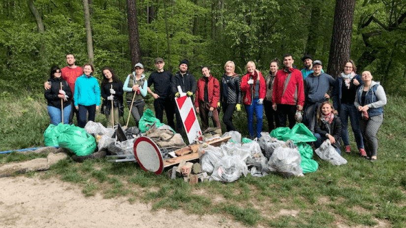 Several people gathered together with a pile of plastics and trash lied in front of them after a long clean up with the forest in the background
