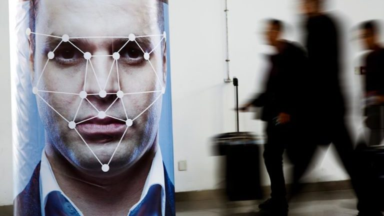Facial recognition poster in thoroughfare with people walking past in background.