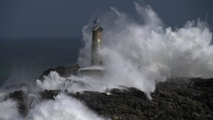 "Waves crash on the lighthouse of ""La Isla del Mouro"" in the port town of Santander, Spain"