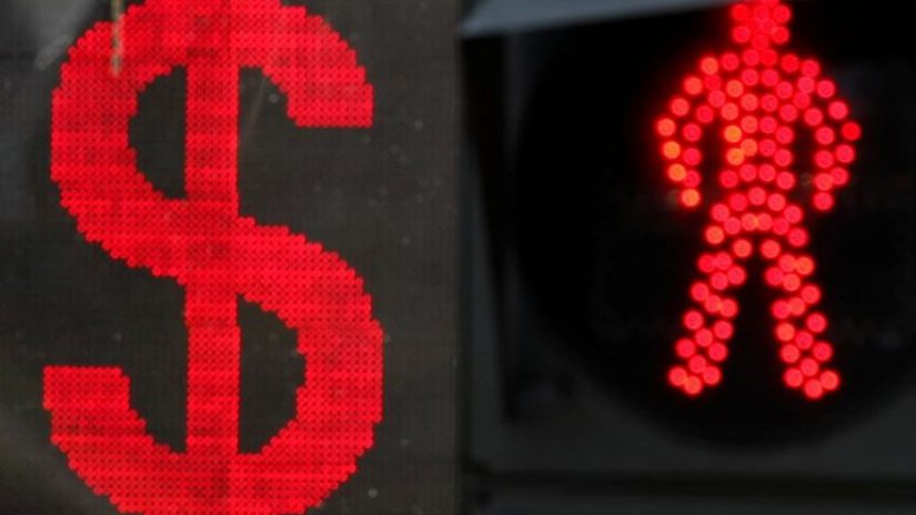 Red US dollar sign shown on electronic board next to a traffic light featuring a red man