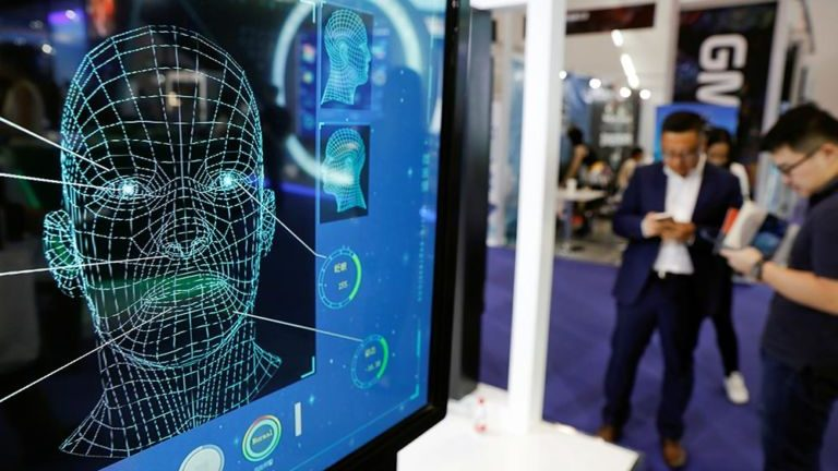 Visitors check their phones behind the screen advertising facial recognition software during Global Mobile Internet Conference (GMIC) at the National Convention in Beijing, China April 27, 2018.