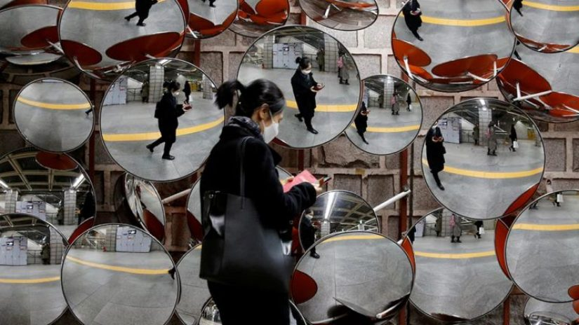 woman wearing mask walking in front of a wall of mirrors