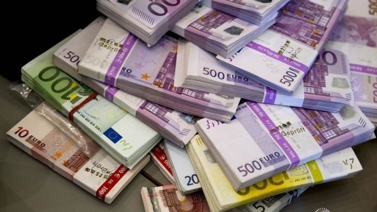 Pile of paper cash in Euros, with wads of 5, 10, 20, 100 and 500 euro notes.