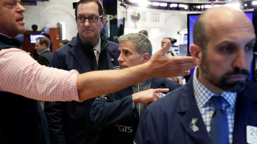 Man pointing out arm directing two others inside stock exchange.
