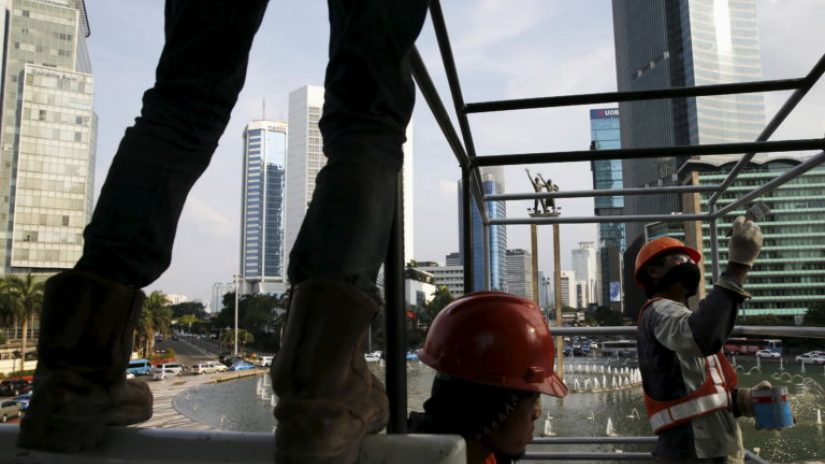 Construction workers build a metal frame with a fountain in the background