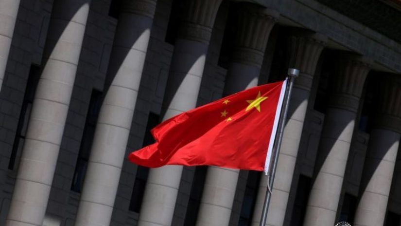 A Chinese flag flutters in front of the Great Hall of the People in Beijing