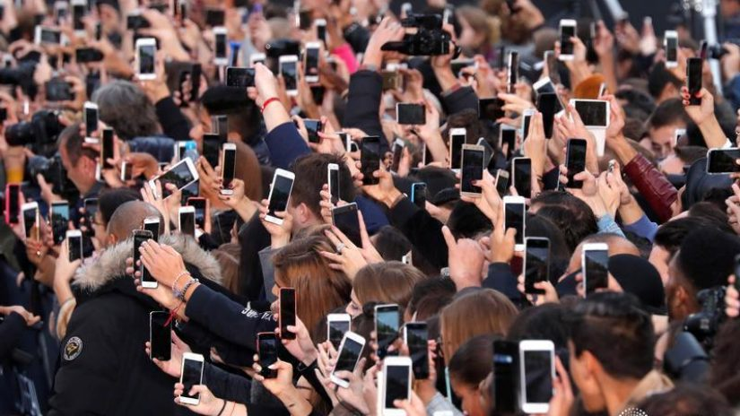 People use their smartphone to take photos of a fashion show.