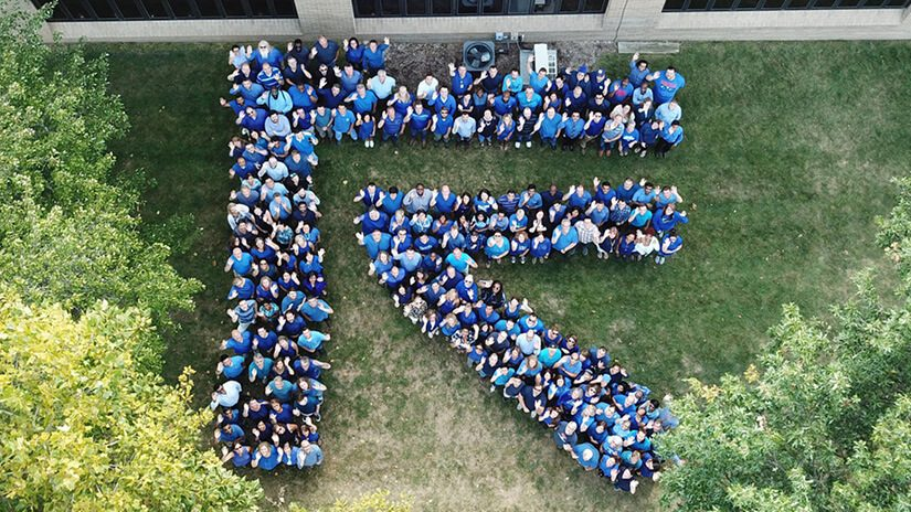 A top down shot of people standing in a garden setting spelling out the letter R