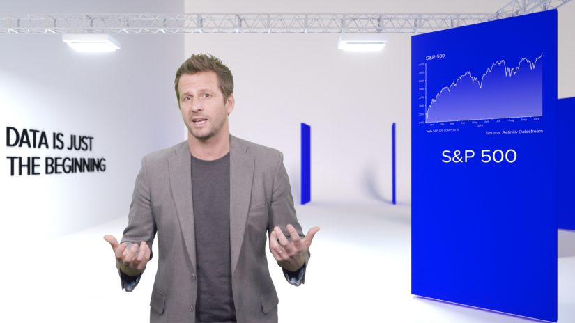 Presenter gestures with hands at center of bright white virtual studio with large presentation panels showing S&P 500 graph.