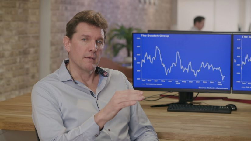 Man gestures to camera in an office setting. Two screens behind him display line charts