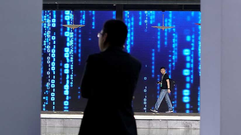 A man walks in front of a screen at the World Internet Conference (WIC) in Wuzhen, Zhejiang province, China