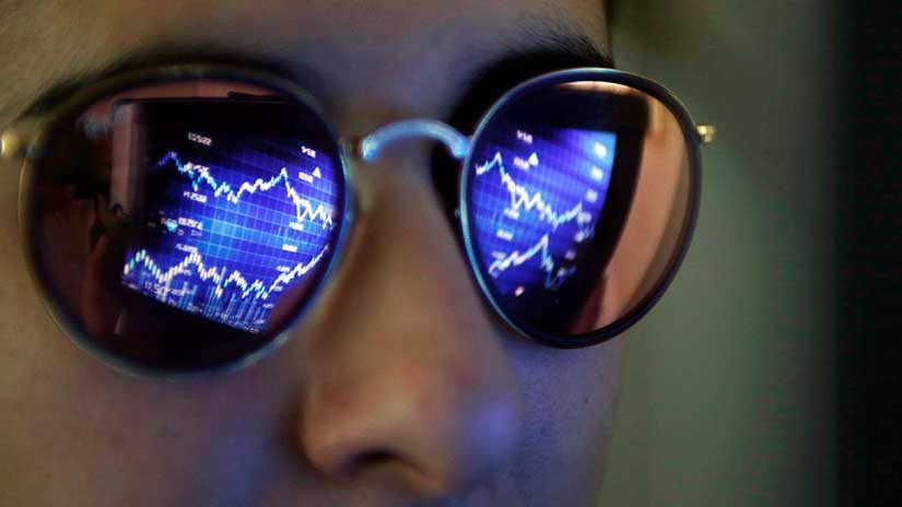 A computer screen showing stock graphs is reflected on glasses in this illustration photo taken in Bordeaux, France