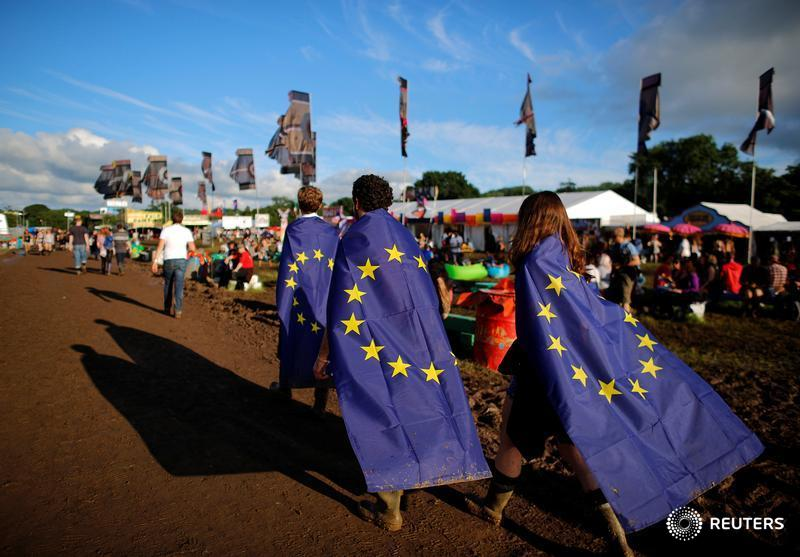 Revellers wrapped in European Union flags walk at Worthy Farm in Somerset during the Glastonbury Festival, Britain, June 22, 2016. REUTERS/Stoyan Nenov - RTX2HNDJ