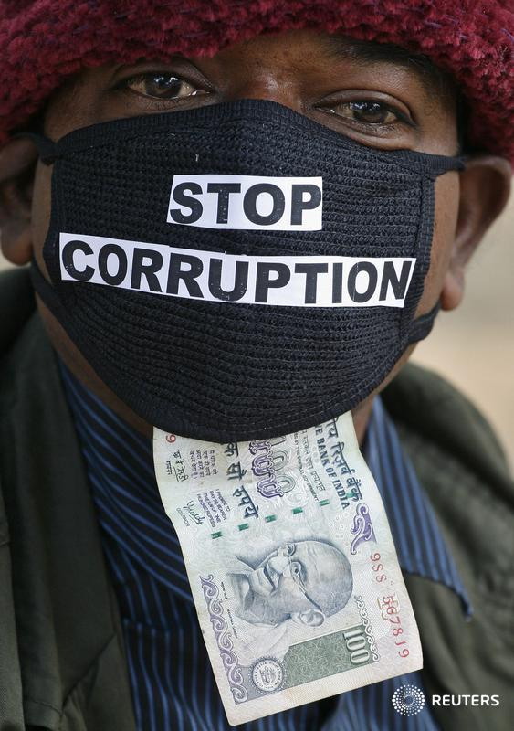 Sajja Murli Chaudhary, 45, an employee of telecom operator systems, displays an Indian currency note as he takes part in a silent protest against the telecom corruption scandal in New Delhi December 9, 2010. Officials of the Central Bureau Investigation (CBI) found what they said were