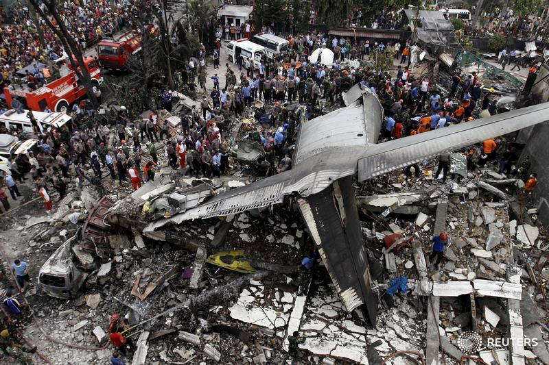 Security forces and rescue teams examine the wreckage of an Indonesian military C-130 Hercules transport plane after it crashed into a residential area in the North Sumatra city of Medan, Indonesia, June 30, 2015. At least 30 people were killed when the military transport plane crashed into a residential area two minutes after take-off in northern Indonesia on Tuesday, putting a fresh spotlight on the country's woeful air safety record. REUTERS/Roni Bintang TPX IMAGES OF THE DAY - RTX1IEBG