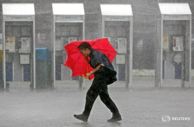 A man walks in the rain along a street in Hong Kong Aug 3, 2006. Typhoon Prapiroon, which killed six people and forced thousands to flee their homes in the northern Philippines, churned towards southern China on Thursday and tens of thousands were evacuated ahead of its arrival. REUTERS/Paul Yeung (HONG KONG) - RTR1G1Q9
