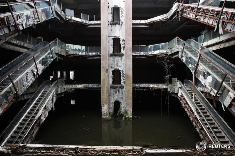 An abandoned department store is seen flooded in Bangkok January 13, 2015. Staff from Bangkok Metropolitan Administration (BMA) office were catching fish on Tuesday at the ground floor of the roofless New World department store that was closed down in 1997. Thousands of fish such as catfishes, fancy carps as well as black and red tilapias were released into the ground floor of the building, flooded with rainwater, as local vendors tried to control mosquitoes in the area, local media reported. BMA recently decided to remove the fish and release the water. REUTERS/Chaiwat Subprasom (THAILAND - Tags: SOCIETY) - RTR4L7VE