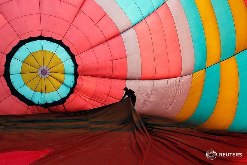 Mifid. A worker adjusts the interior of a hot air balloon before its take off on the banks of the river Ganges in Allahabad