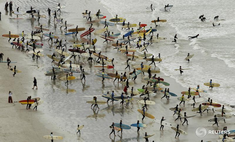 South African surfers take to the water in an attempt to break the Guinness World Record for the highest number of riders on a single wave at Muizenberg in Cape Town