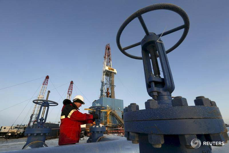 A worker checks a valve of an oil pipe at the Imilorskoye oil field, Kogalym, Russia. Photography: Sergei Karpukhin