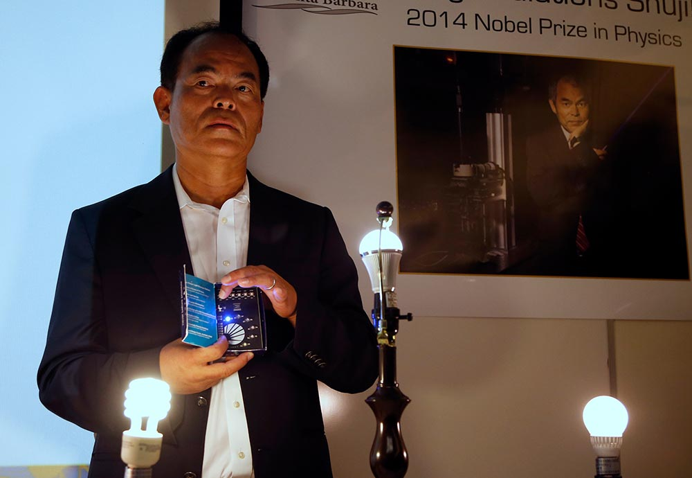 Japanese-born U.S. citizen Shuji Nakamura holds a blue LED light at a news conference after winning the 2014 Nobel Prize for Physics, at the University of California Santa Barbara in Isla Vista, California. Celebrating prize-winning innovation in Japan