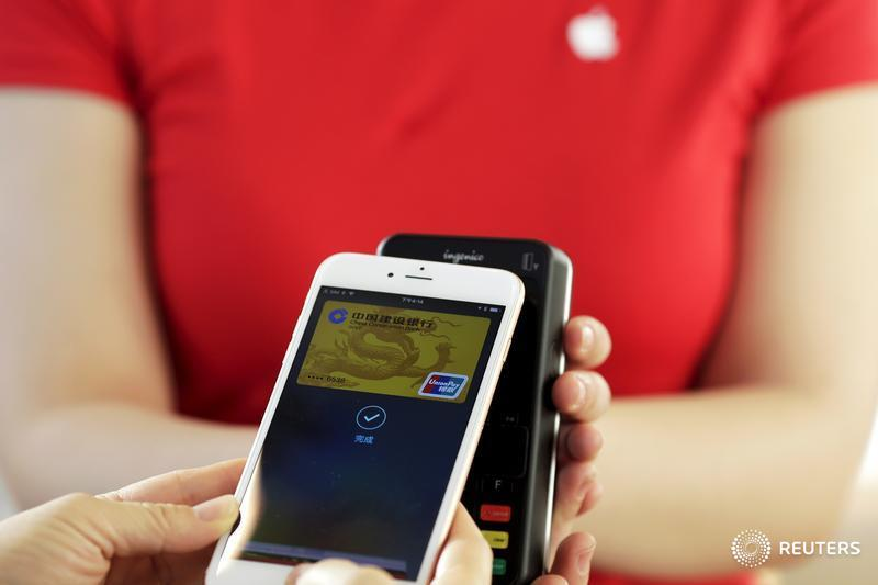 Employees use an Apple iPhone to demonstrate the Apple Pay service in Beijing