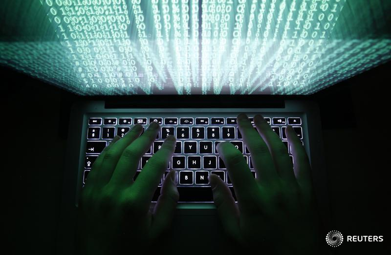 Illustration file picture shows a man typing on a computer keyboard in Warsaw